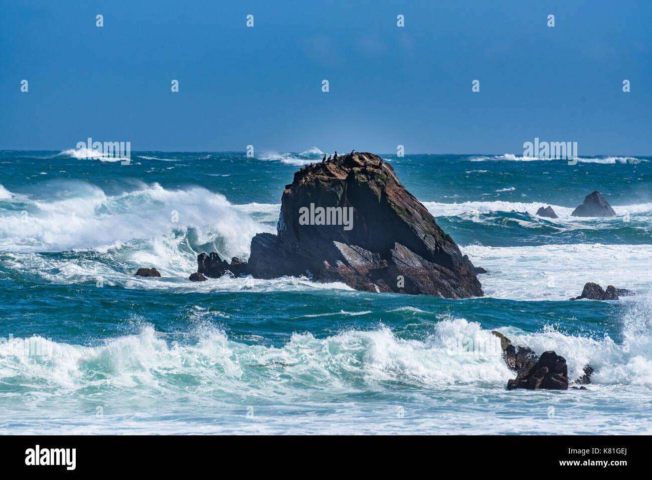 Waves crash against the rocks along the Alaskan Coast - Stock Image