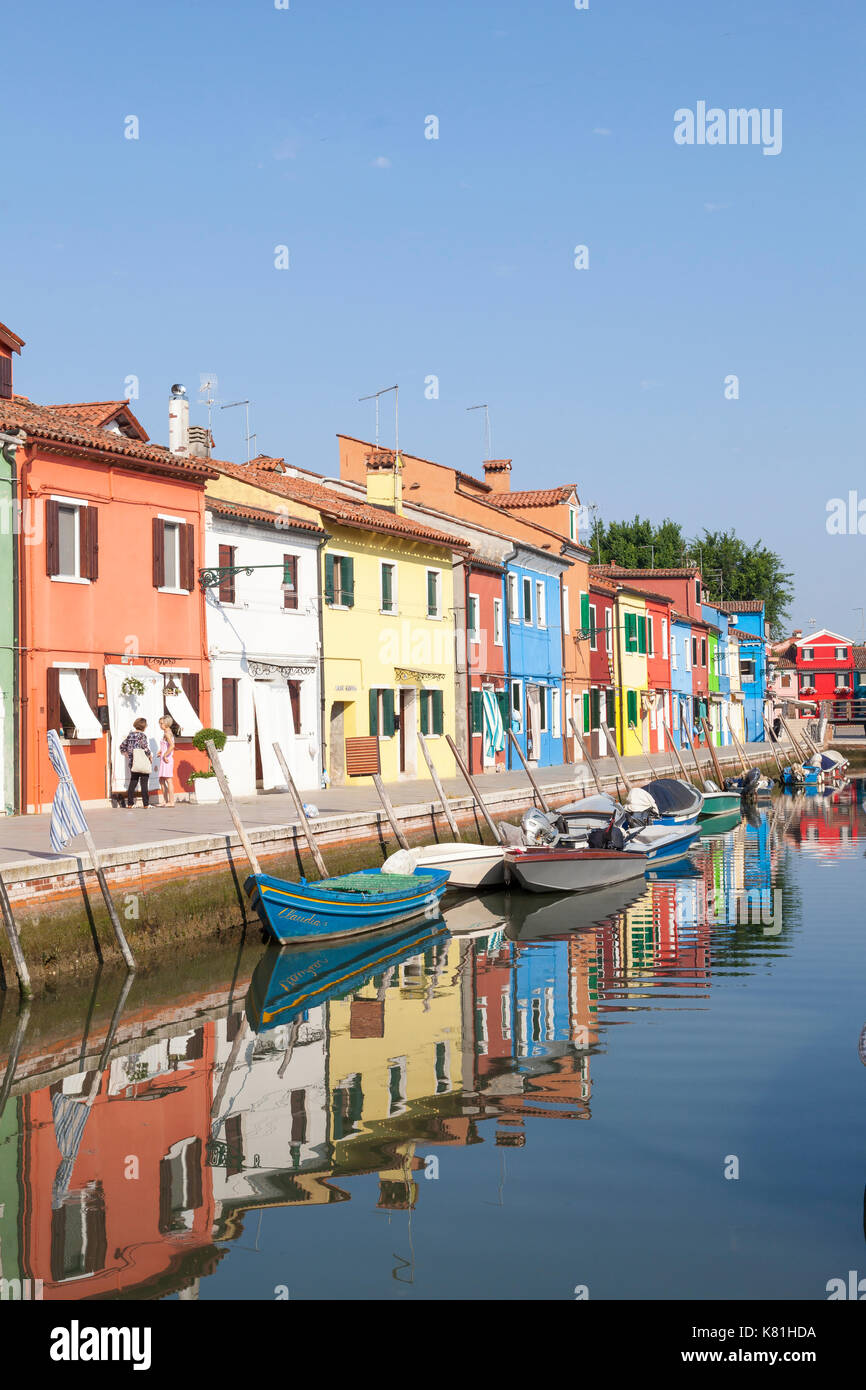 Colorful houses on Burano, Venice,  Veneto, Italy in early morning light reflected in the still water of the canal below - Stock Image