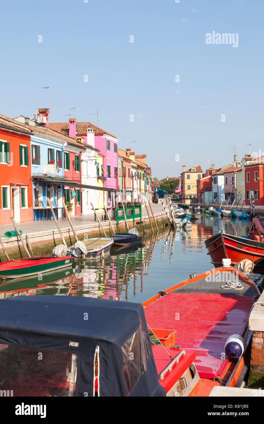 Colorful red, work boats at sunrise in a canal on  Burano, Venice, Veneto,  Italy lined with brightly painted houses reflected in the water below. - Stock Image