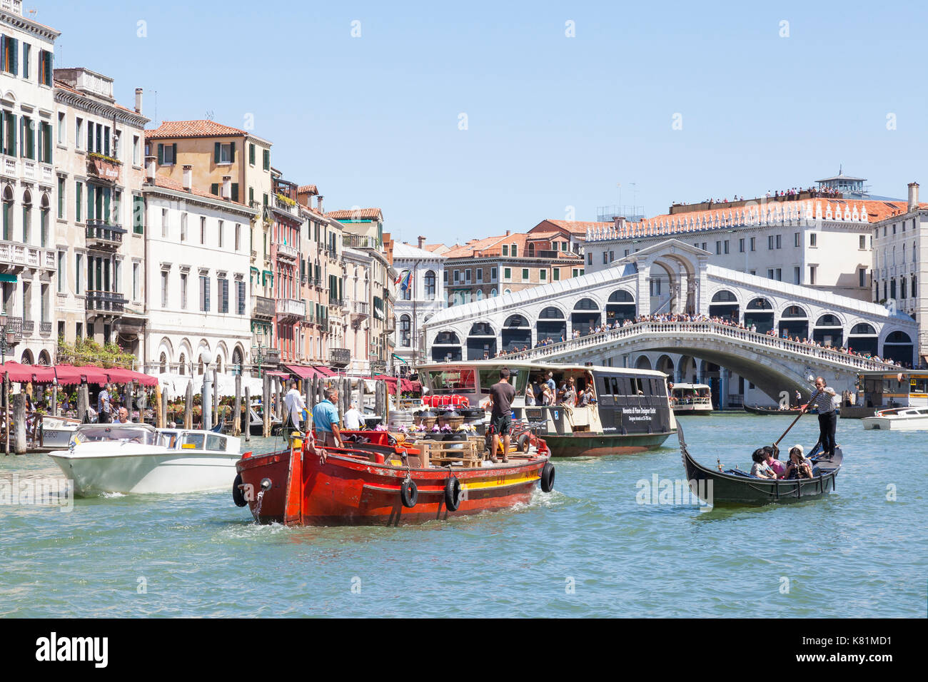 Busy boat traffic on the Grand Canal below the Rialto Bridge, Venice, Italy with a gondolier rowing tourists in a gondola, water taxi, work barge tran - Stock Image