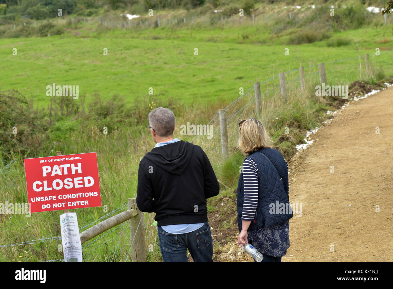 A 'road closed' 'path closed 'sign and a couple a man and a woman walking past and ignoring the instruction or warning. Disregarding safety notices. - Stock Image