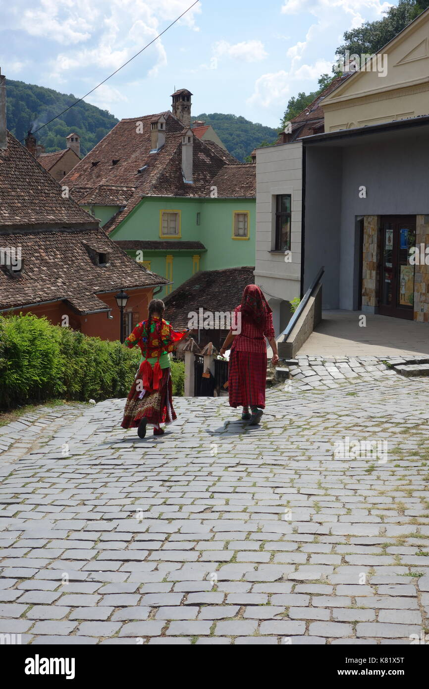 Gypsy walking in Sighisoara town's hilly streets with their original medieval architecture. Transylvania, Romania - Stock Image