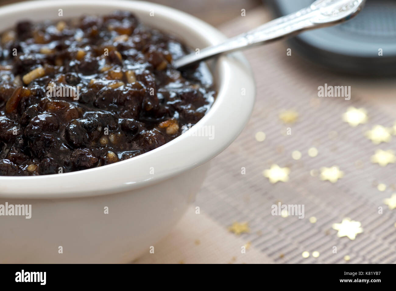 macro image of homemade traditional Christmas mincemeat made with mixed fruit and brandy in a white bowl, focus Stock Photo