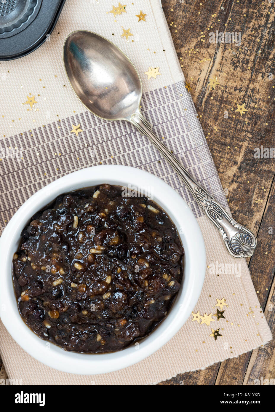 vertical image of homemade traditional Christmas mincemeat made with mixed fruit and brandy in a white bowl, focus on the subject , background de focu - Stock Image