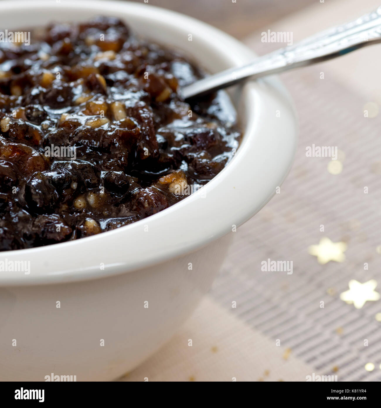 square macro image of homemade traditional Christmas mincemeat made with mixed fruit and brandy in a white bowl, focus on the subject,   background de - Stock Image