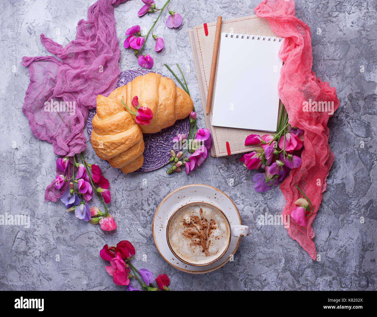 Coffee, croissants, flower and notebook.  - Stock Image