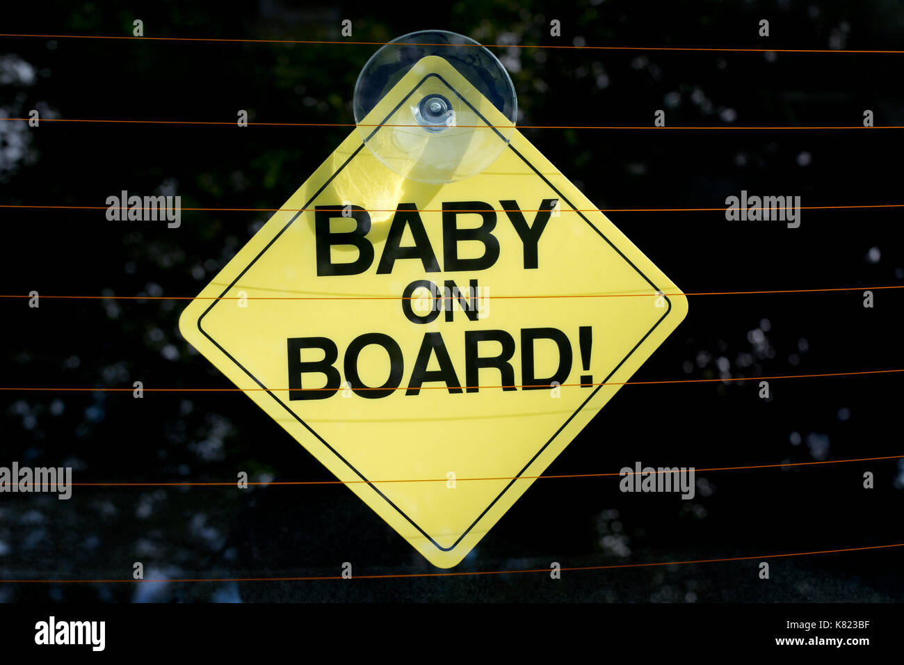 A sign shot through the rear window of a car indicating there is a baby on board in the vehicle. - Stock Image