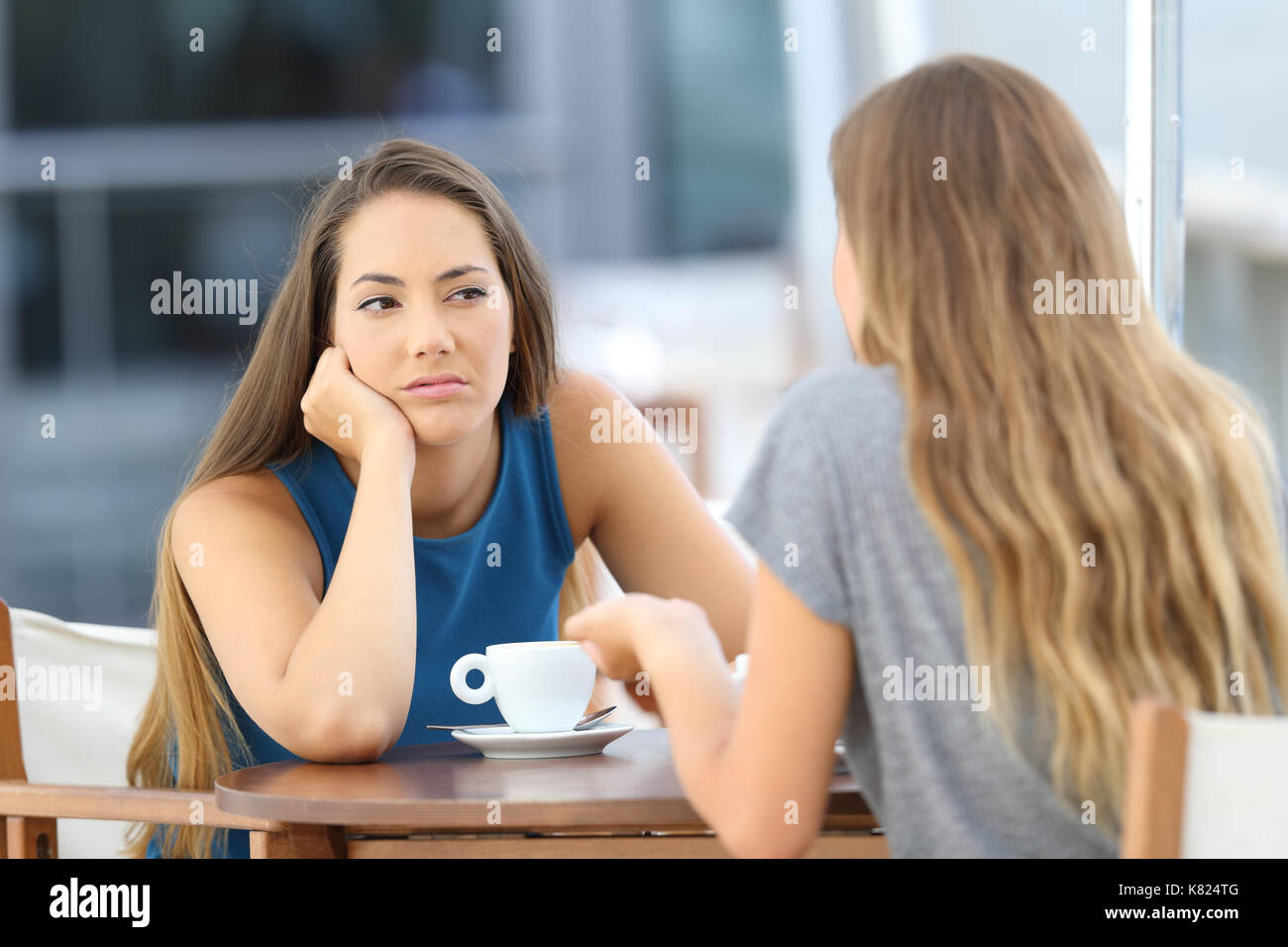 Bored girl listening a bad conversation sitting in a restaurant terrace - Stock Image
