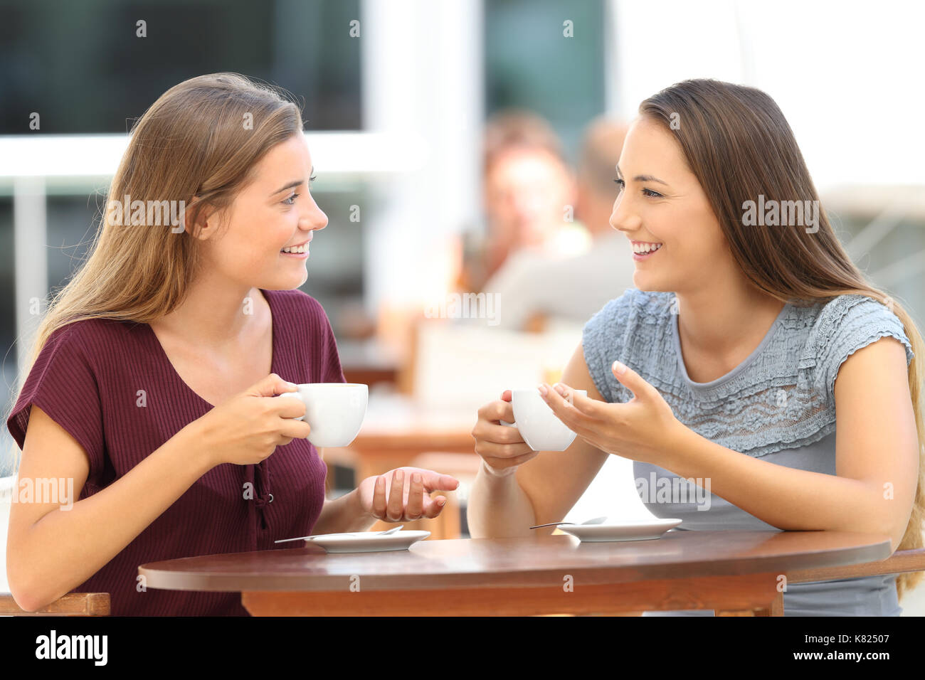 Two happy friends having a good conversation sitting in a bar terrace Stock Photo