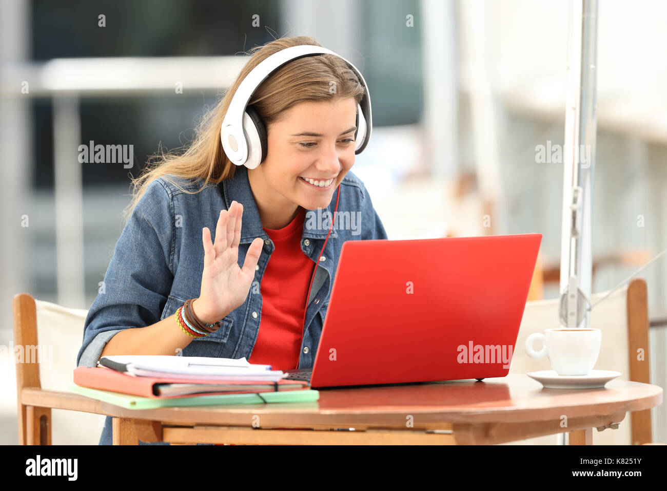 Happy student having a video conference with a red laptop and headphones sitting in a bar terrace - Stock Image