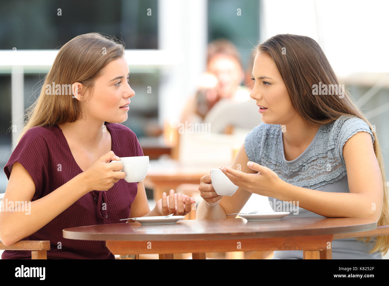 Two serious friends talking sitting in a restaurant - Stock Image