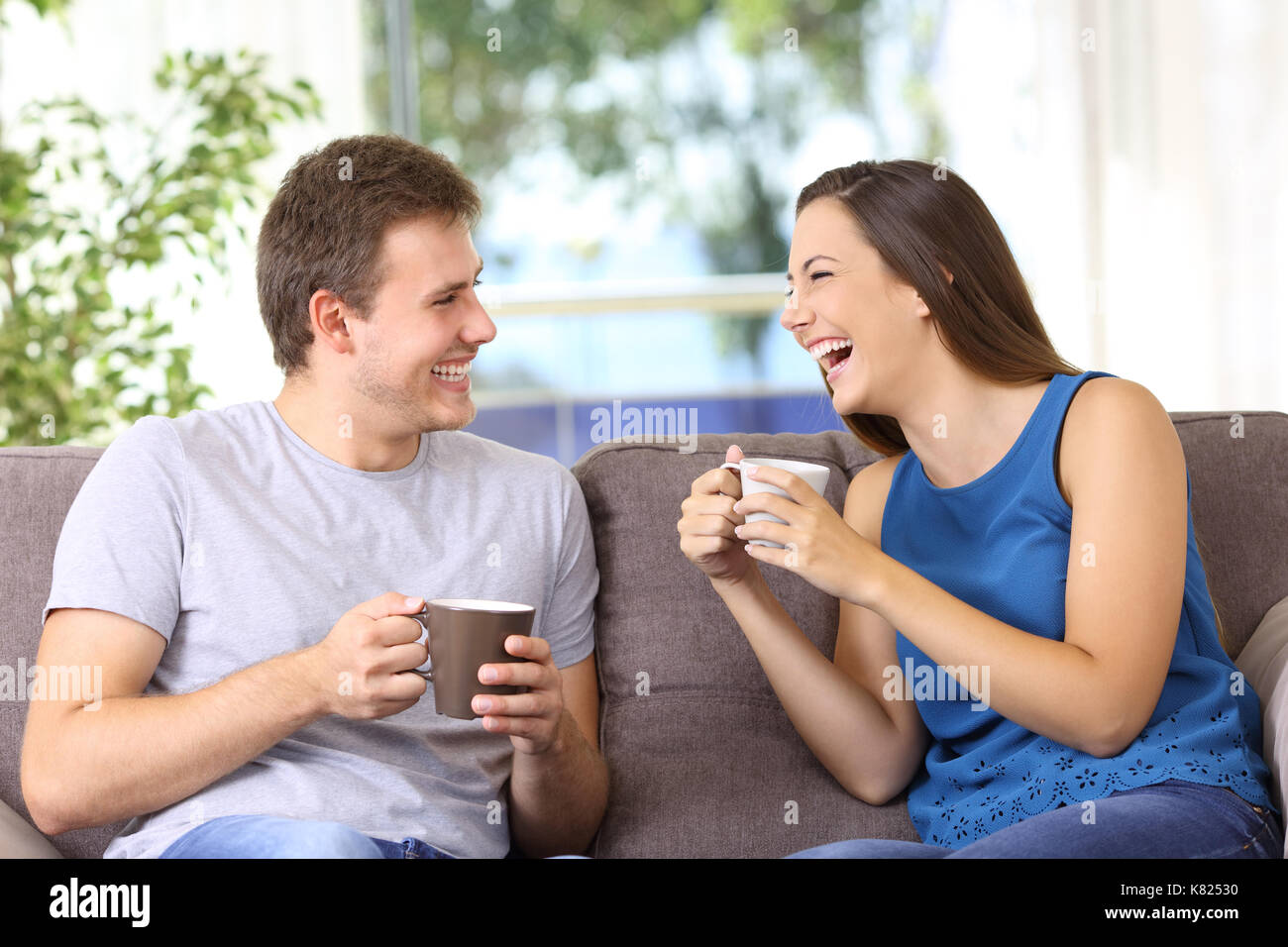 Two people talking and laughing loud sitting on a sofa at home - Stock Image