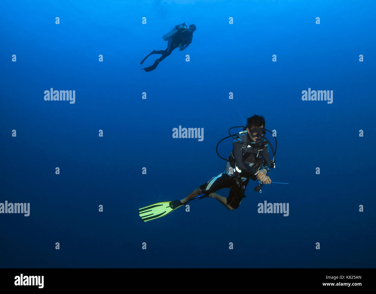 Malaysian dive master leads scuba diver into the deep blue in search of pelagic marine wildlife. Spratly Islands, South China Sea. - Stock Image