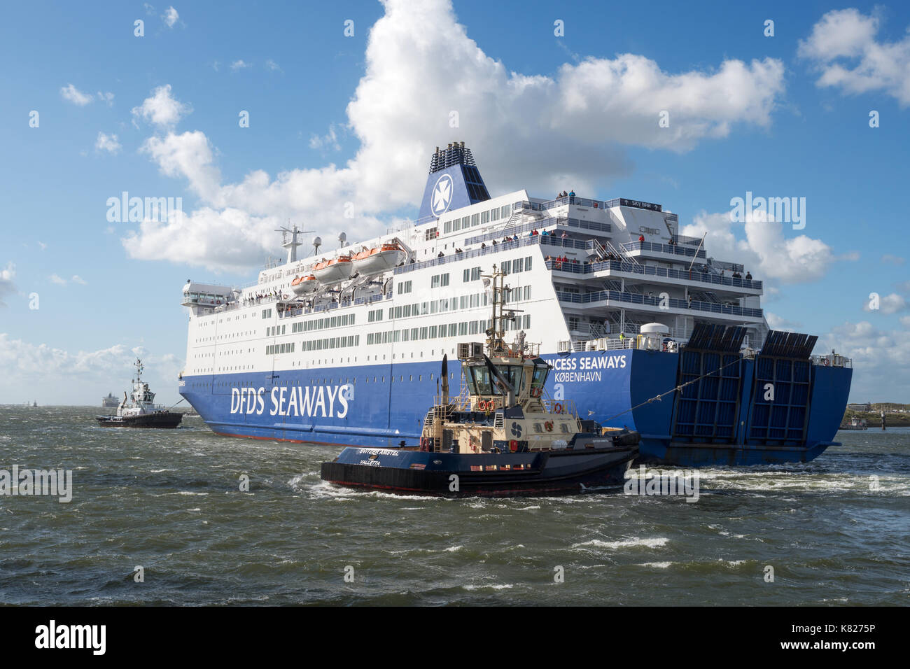 DFDS north sea ferry Princess Seaways being assisted into Ijmuiden port by tugs due to strong onshore winds, Holland, Europe - Stock Image