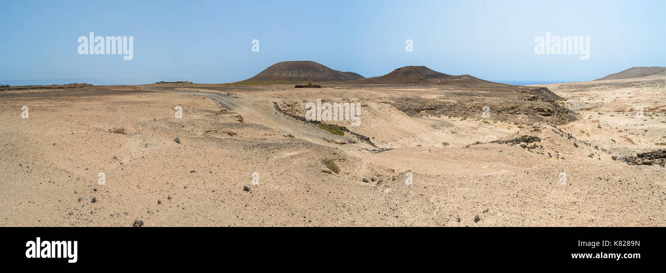 sand dunes and rocks of Fuerteventura island with volcanoes in the background, Canary - Stock Image
