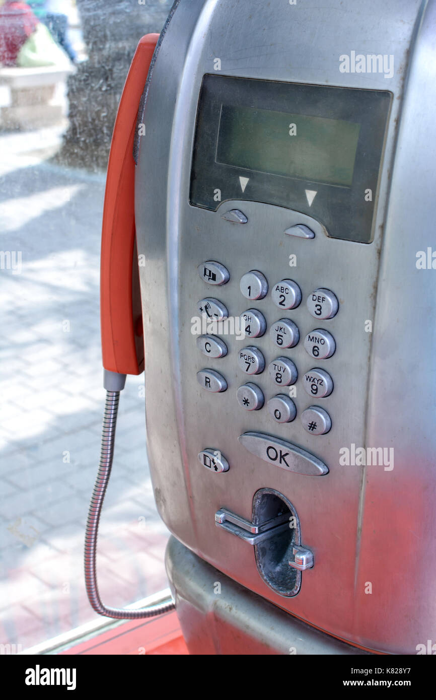 old public telephone booth running with tokens and tiles - Stock Image