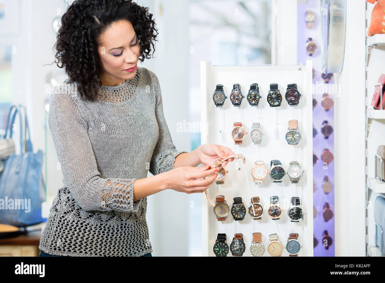 Young woman in jewellery store looking for wristwatches - Stock Image