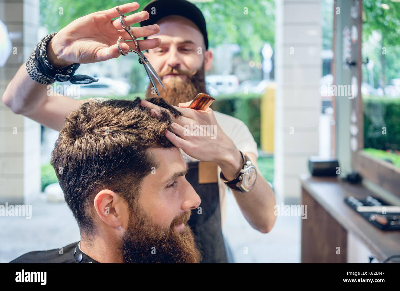 Dedicated hairstylist using scissors and comb while giving a coo - Stock Image