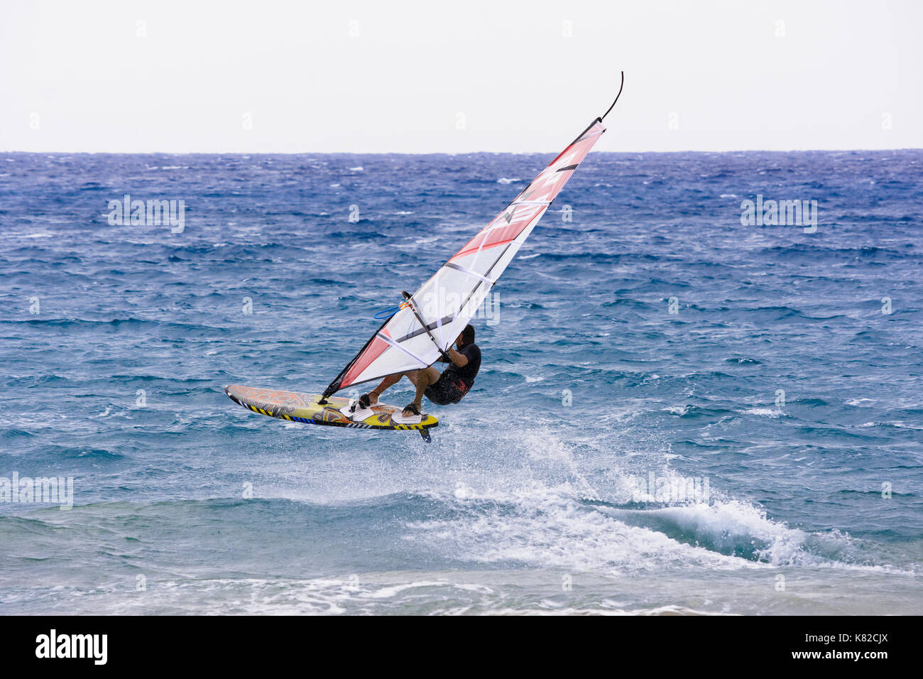 windsurfer that drives its windsurfing speed through the sparkling waves of the Ligurian Sea, in Mediterranean Sea - Stock Image
