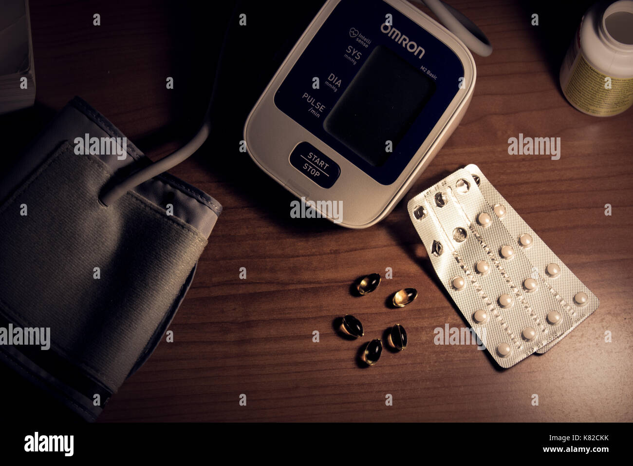 blood pressure monitor and pills on a desk - Stock Image