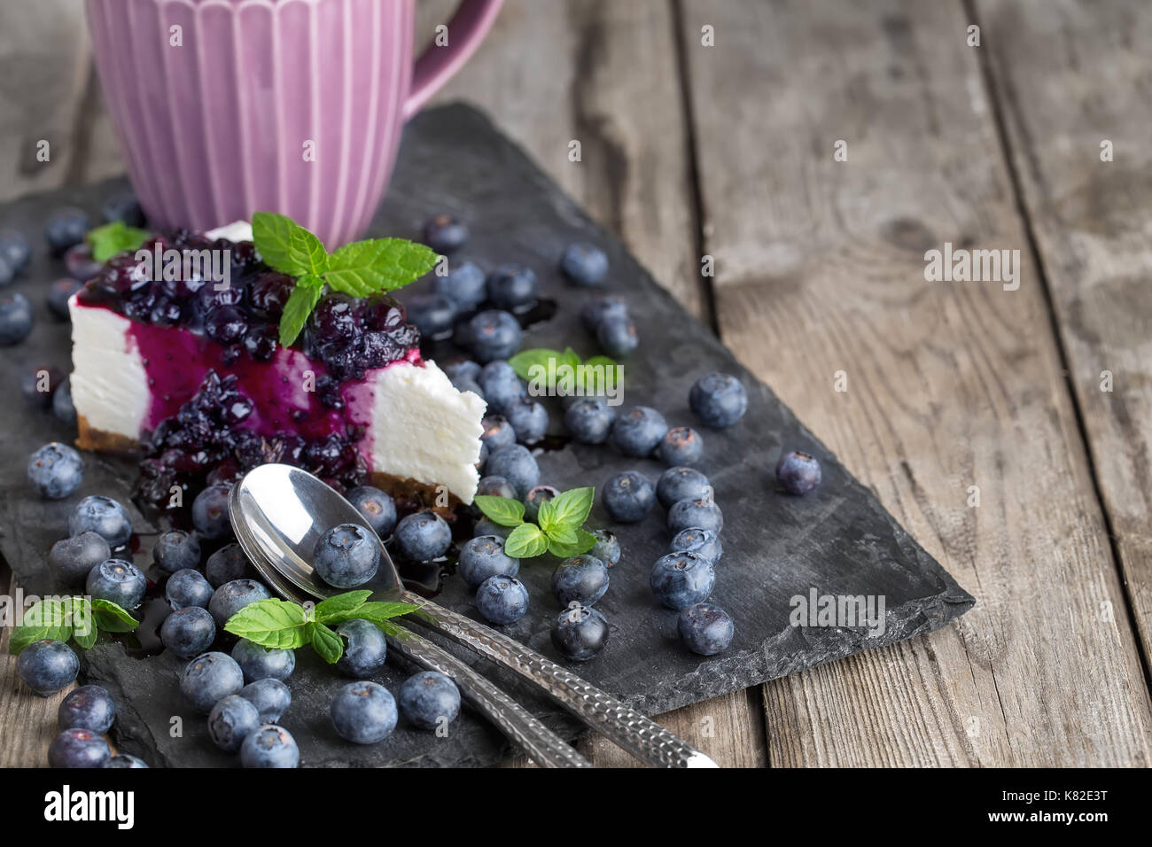 Piece of homemade cheesecake with blueberry jam and fresh ripe blueberries.Copy space background. - Stock Image