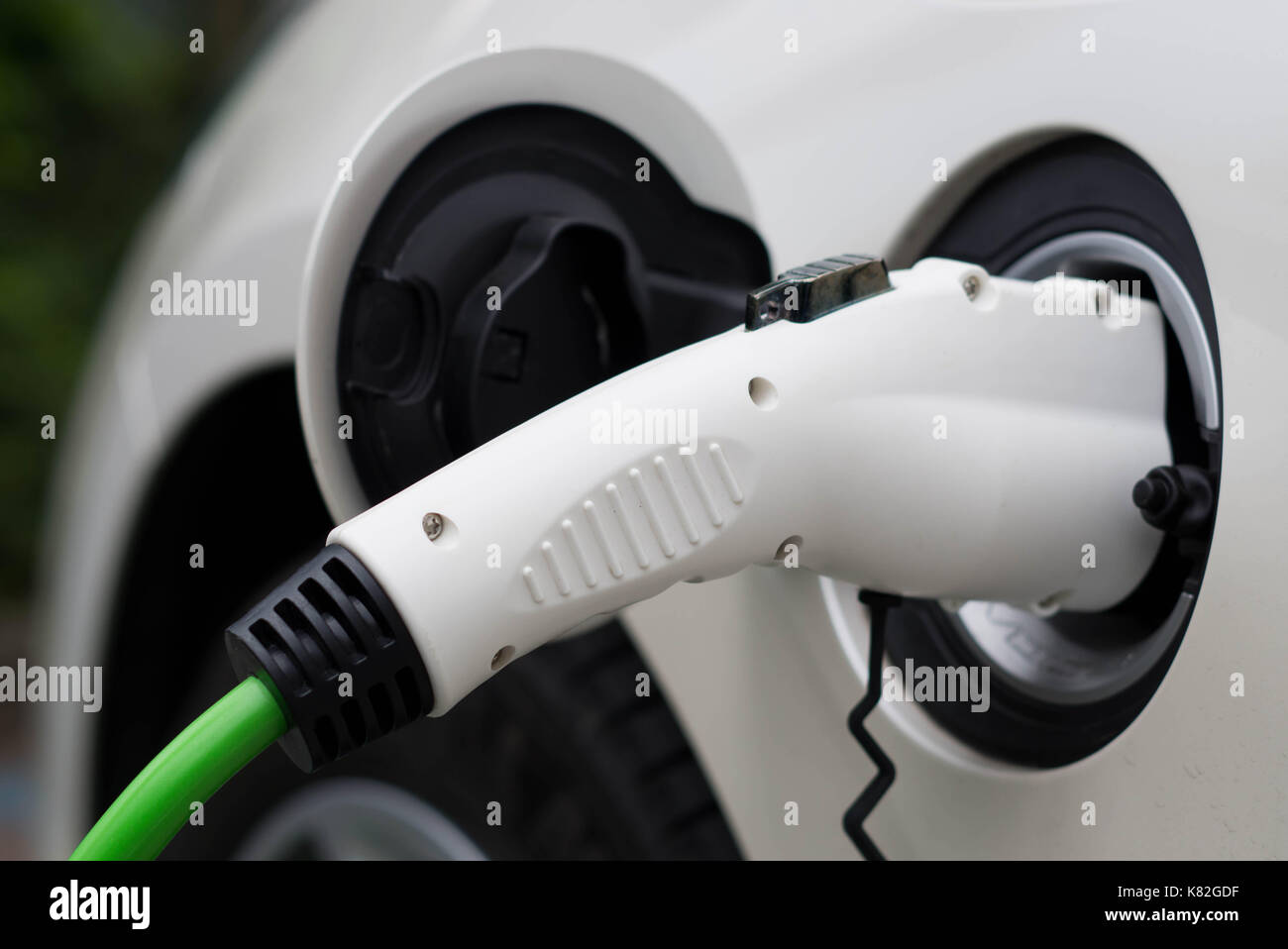 Electric car charging station. Close up of the power supply plugged into an electric car being charged. Stock Photo