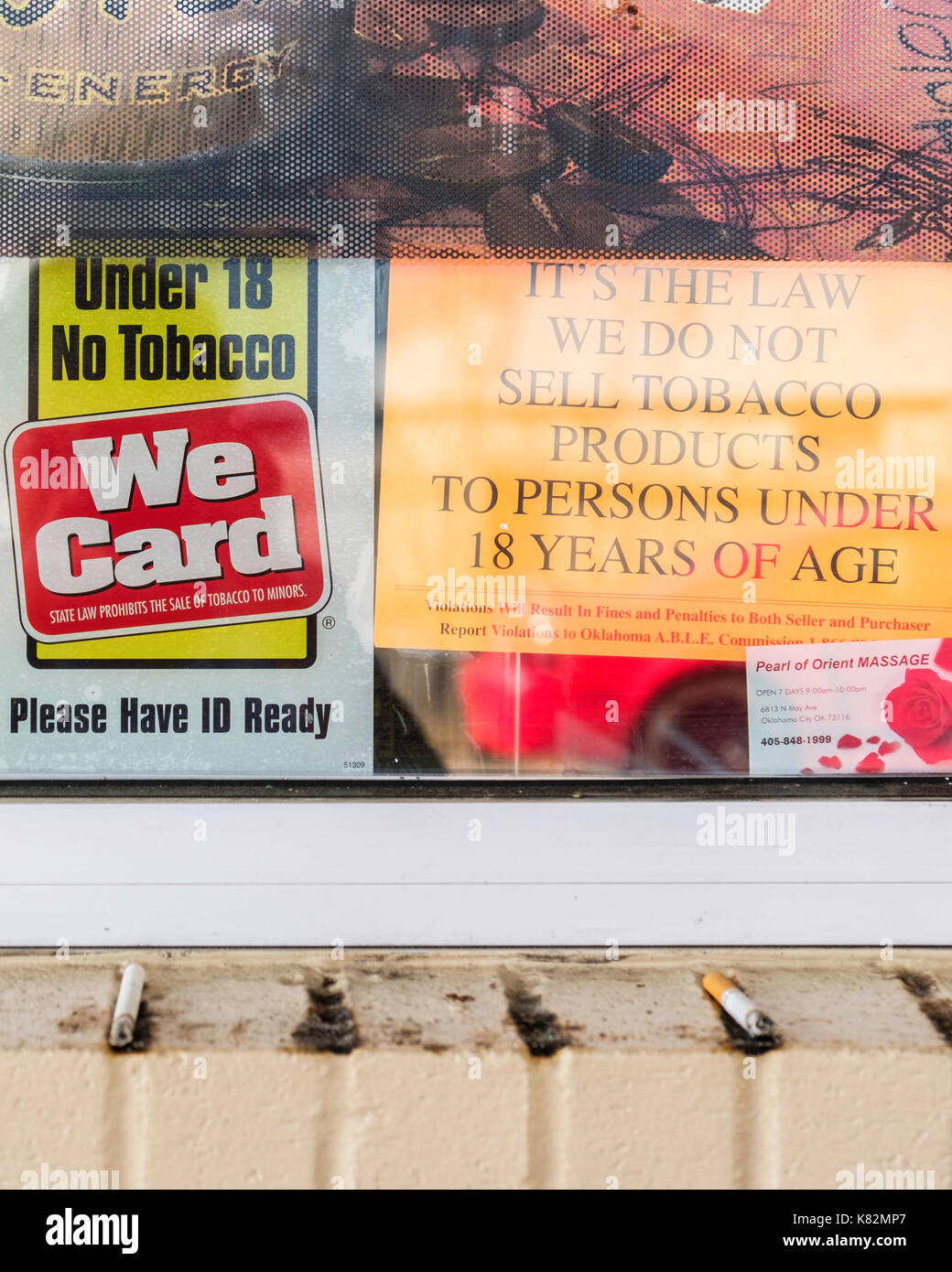 A gasoline station window displaying warning signs about minors buying tobacco. Oklahoma City, Oklahoma, USA. - Stock Image