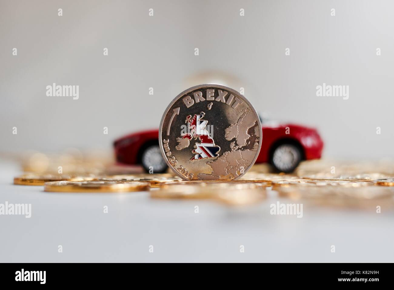Europe leaving. Physical brexit coin near red luxury car. British map flag. Stock Photo