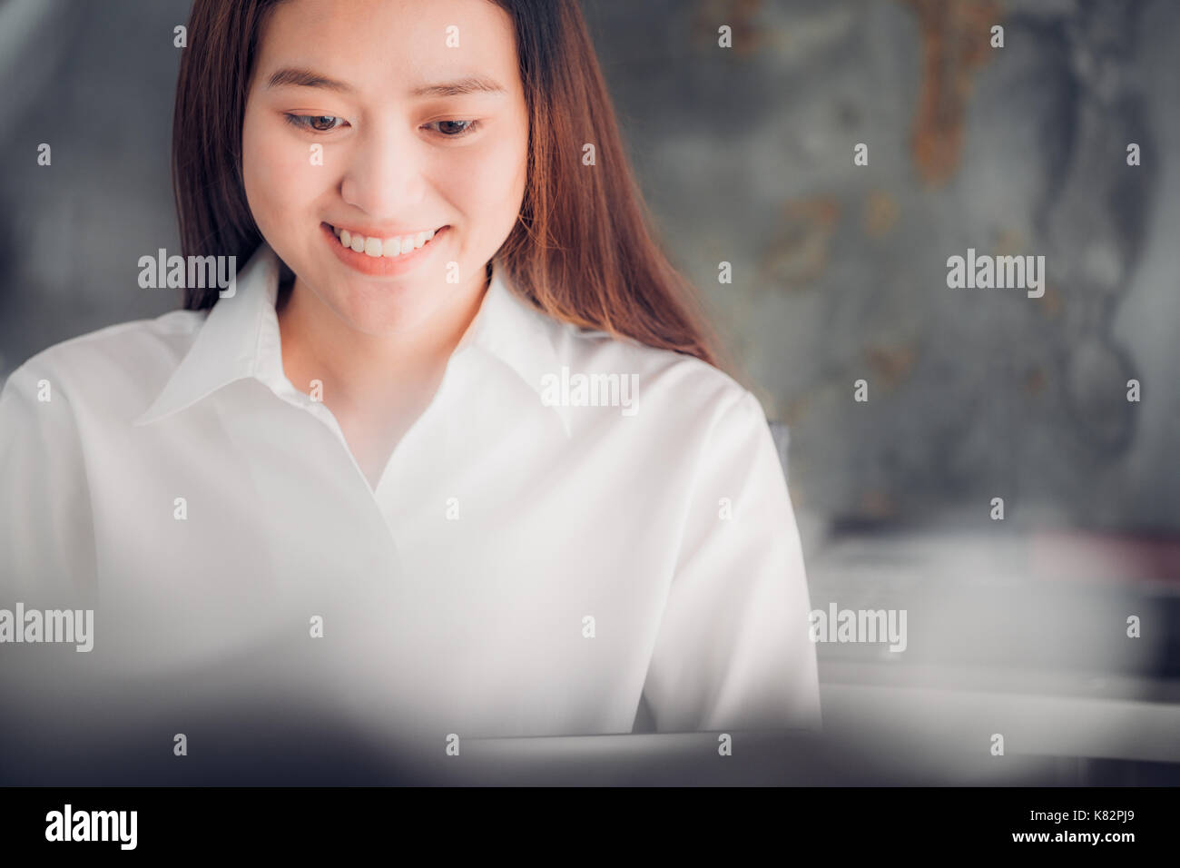 Asian businesswoman looking at laptop computer and smiling face with happy emotion from good news of business success - Stock Image