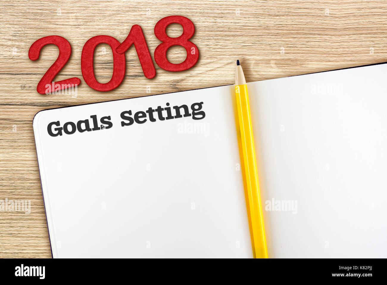 top view of 2018 new year red number and goals setting with blank open notebook and yellow pencil on wooden table topmock up for adding your content
