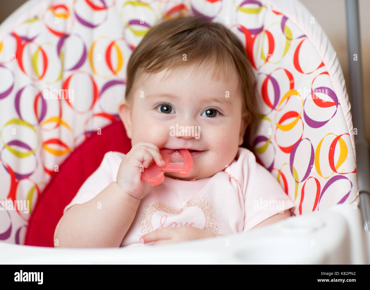 Cute baby chewing on teething toy. First teeth. - Stock Image