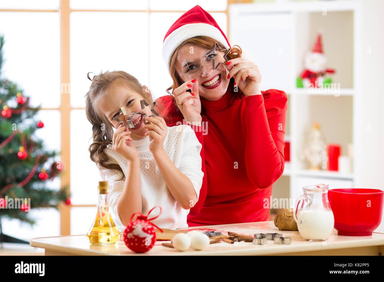 Mother and daughter baking Christmas cookies. Child and woman jokes around with shape for modeling - Stock Image