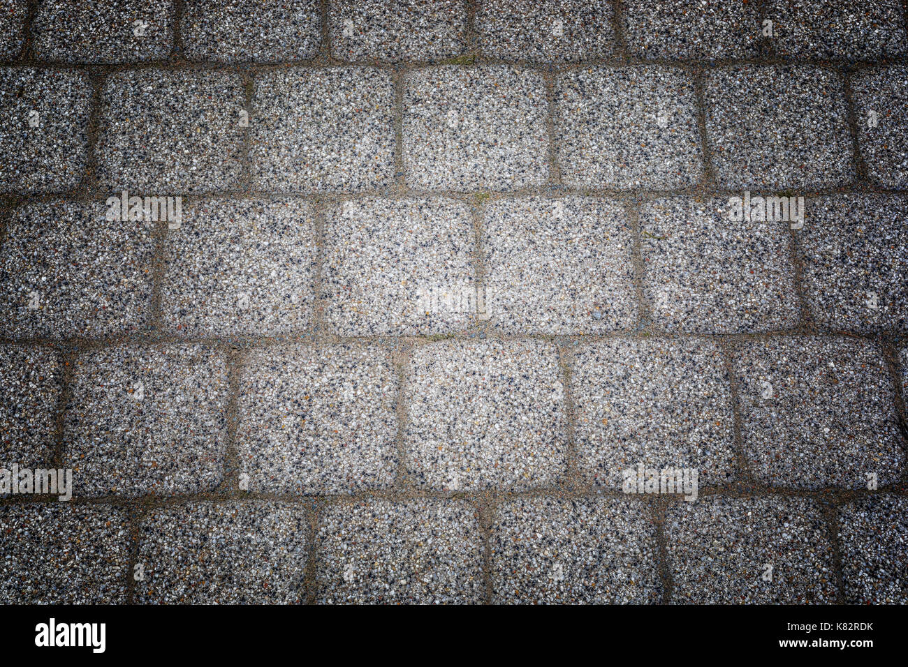 Abstract background of old cobblestone pavement texture with natural patterns view from above. - Stock Image