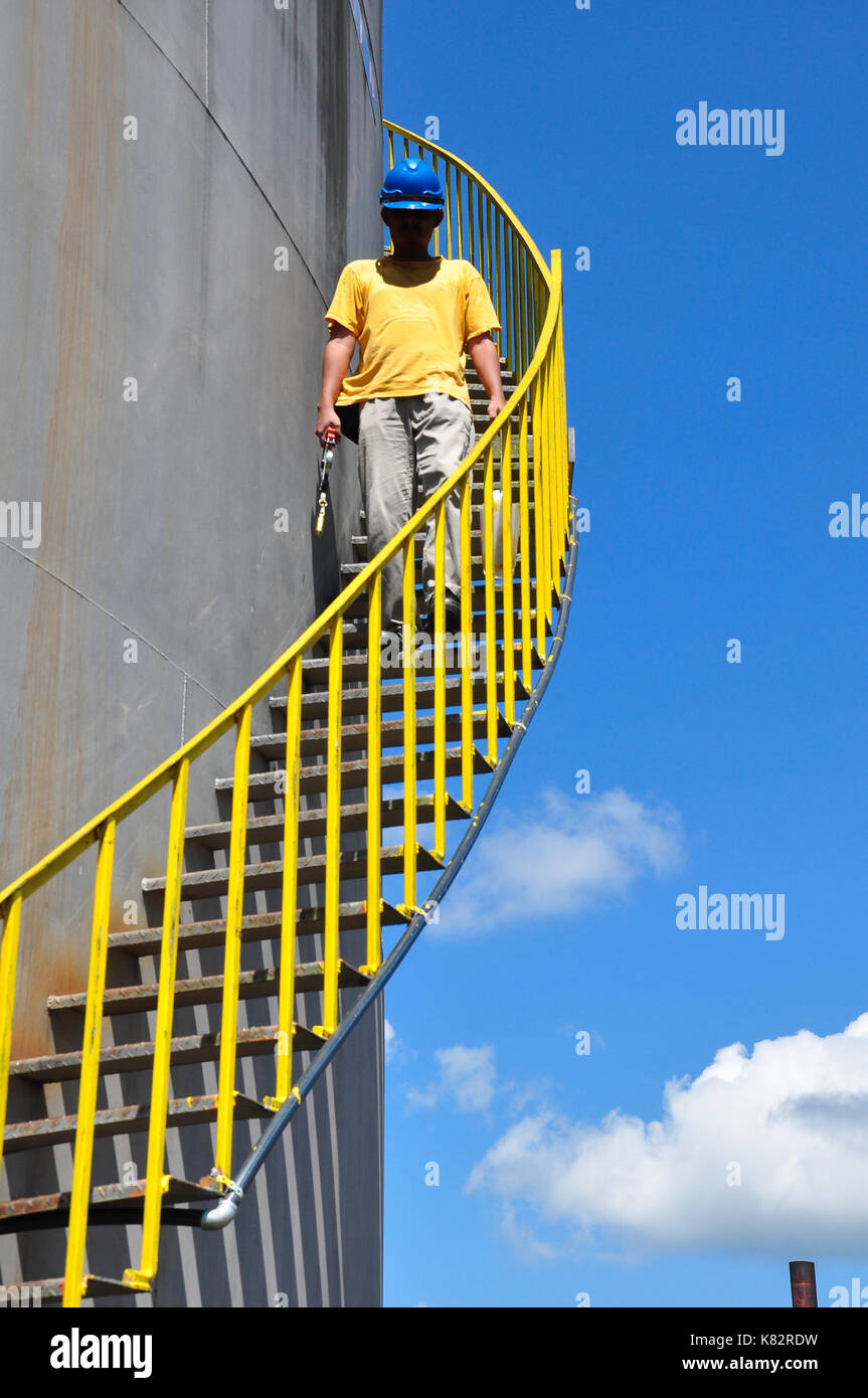 Worker get down from the palm oil stock tank - Stock Image