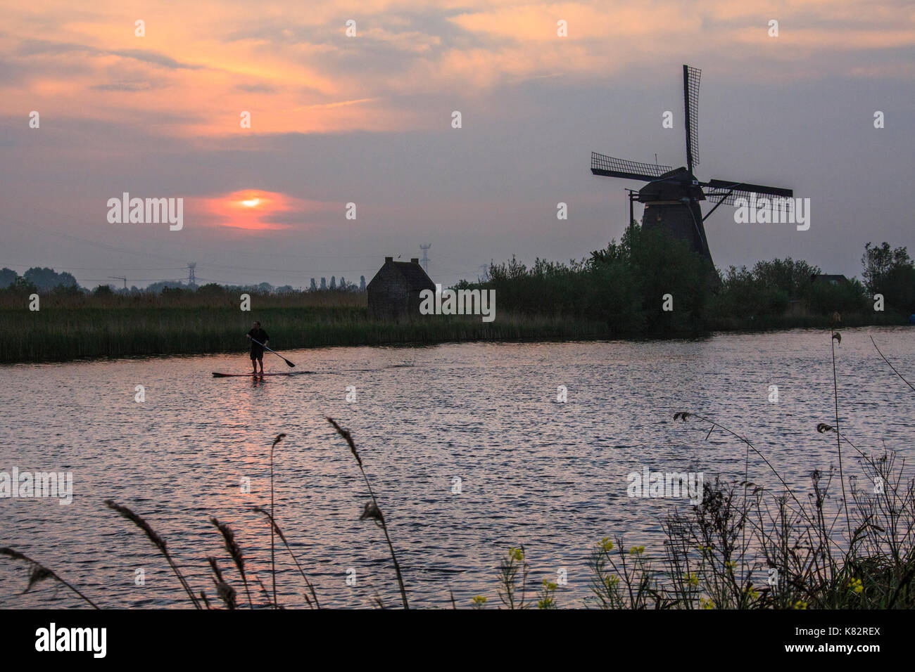 Sunrise on the windmill reflected in the canal Kinderdijk Rotterdam South Holland Netherlands Europe Stock Photo