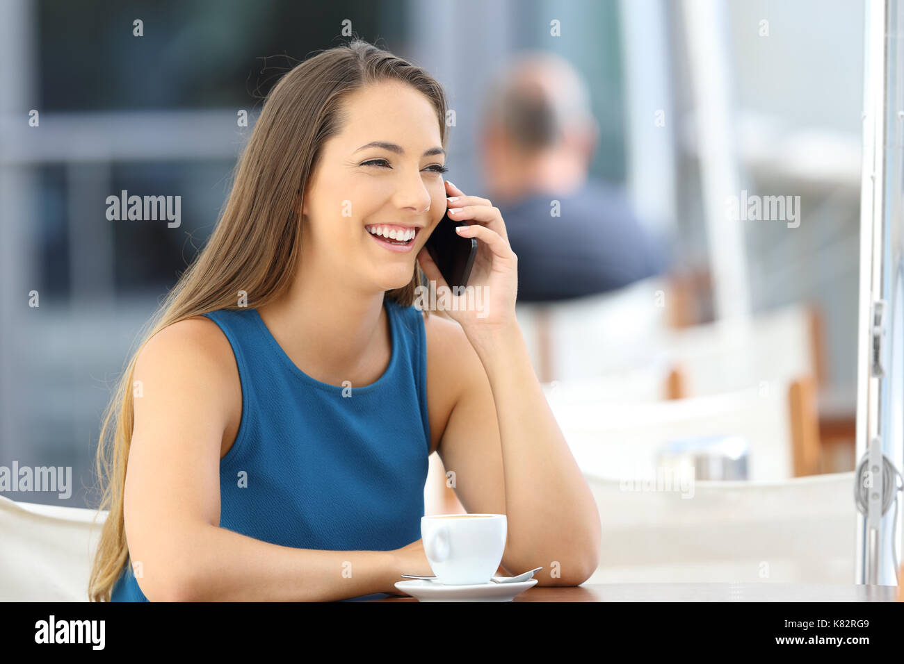 Single woman having a phone conversation sitting in a bar terrace - Stock Image