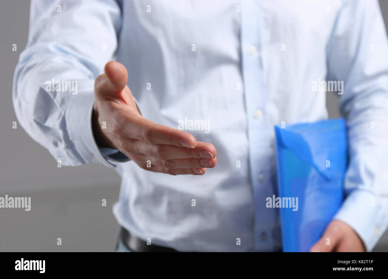Businessman offering his hand for handshake - Stock Image