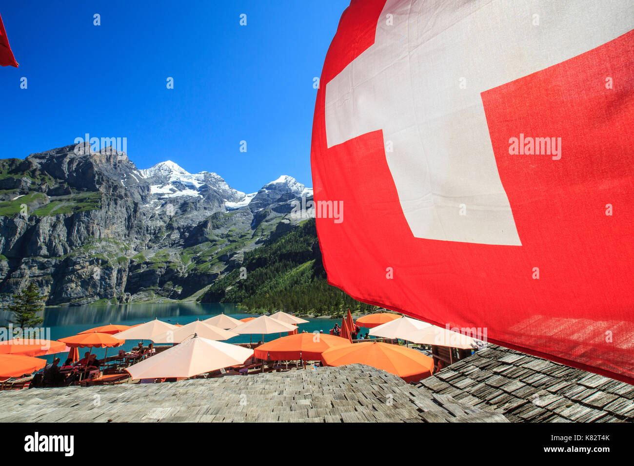Tourists relaxing at Lake  Oeschinensee Bernese Oberland Kandersteg Canton of Bern Switzerland Europe - Stock Image