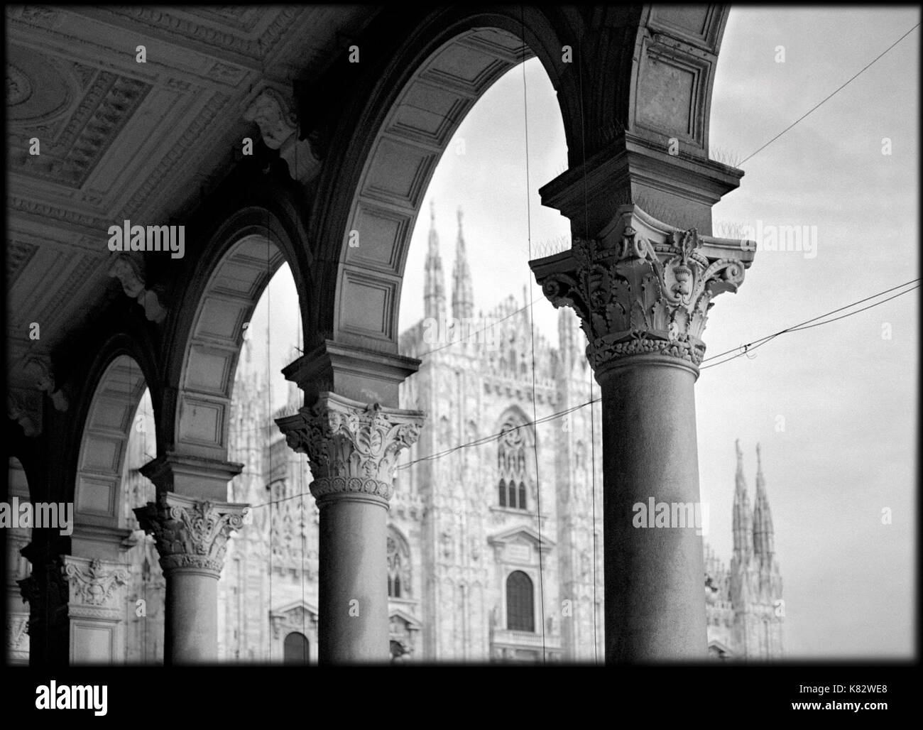 Italy, Lombardy, Milan, View Of The Duomo Through Columns - Stock Image