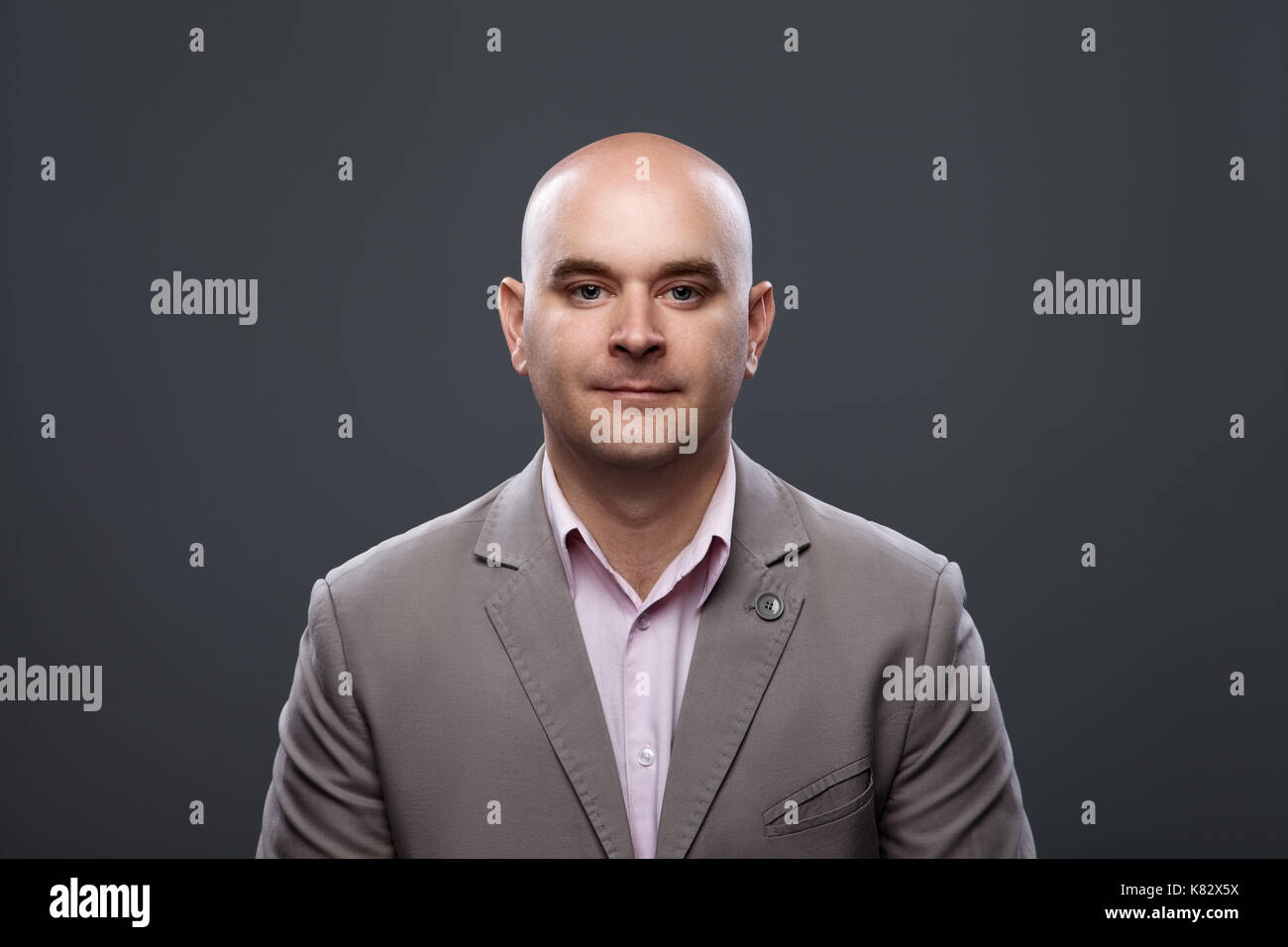 Portrait of a bald affable man in a suit against a dark background, studio shot. - Stock Image