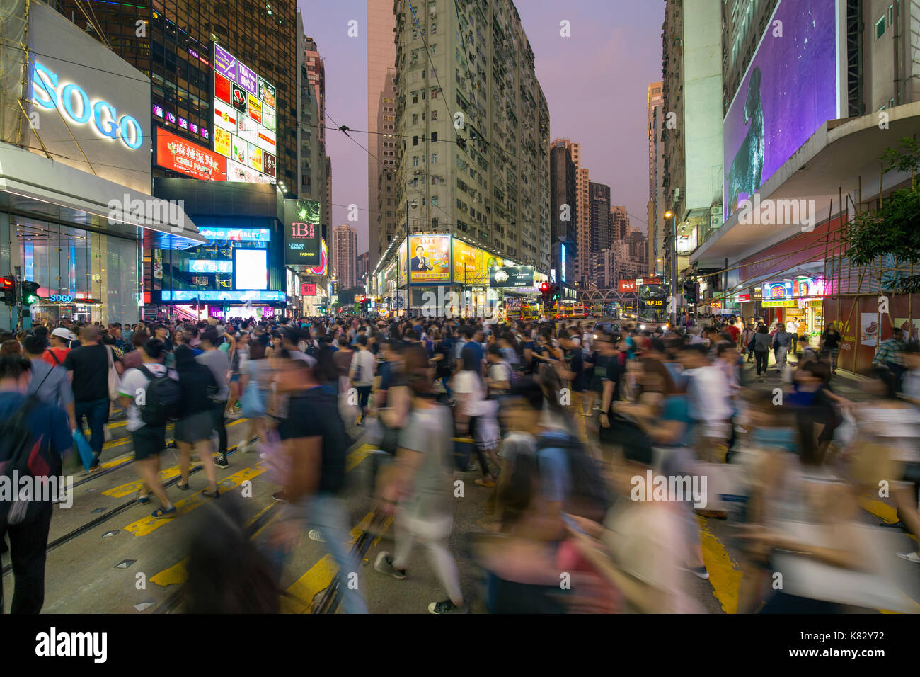 Pedestrians and traffic at a busy road crossing in Causeway Bay, Hong Kong Island, Hong Kong, China - Stock Image