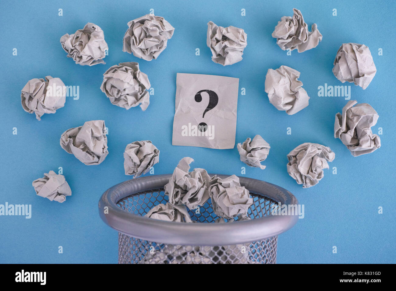 Gray crumpled paper balls and question mark rolling out of a trash can. Close up. - Stock Image