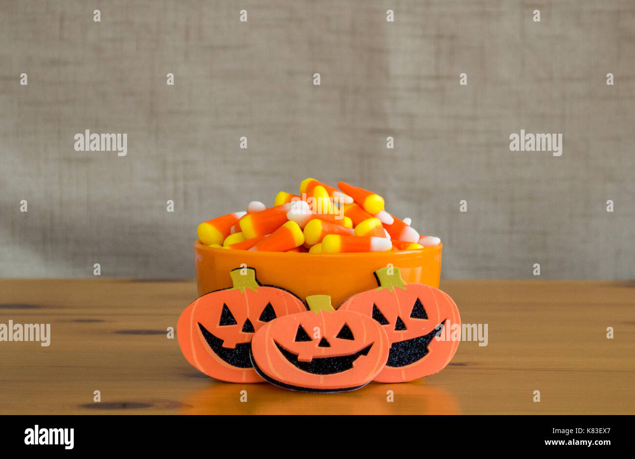candy corn in an orange bowl with mini jack-o-lantern cartoons on a wooden table - Stock Image