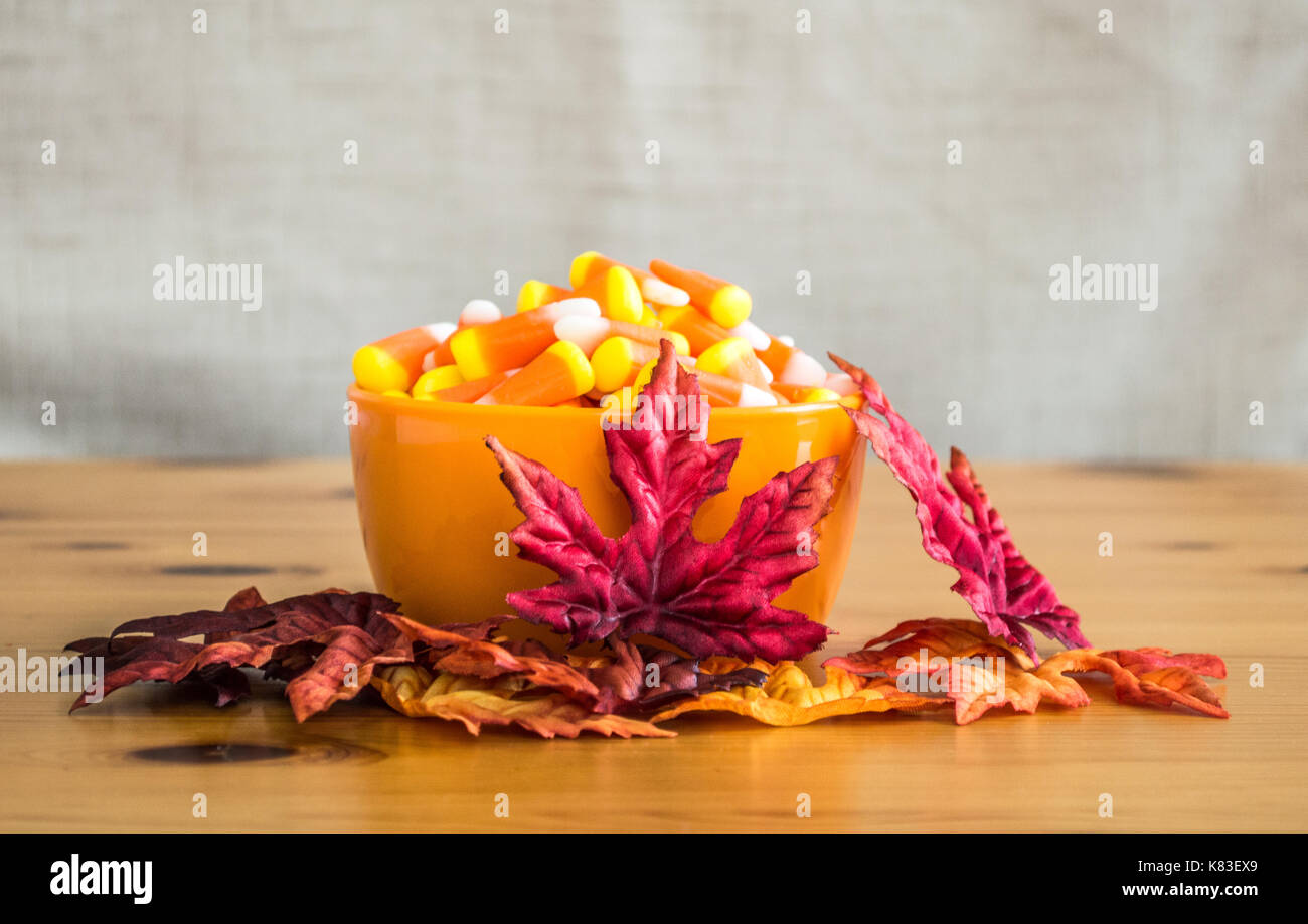 candy corn in an orange bowl with colorful autumn leaves on a wooden table - Stock Image