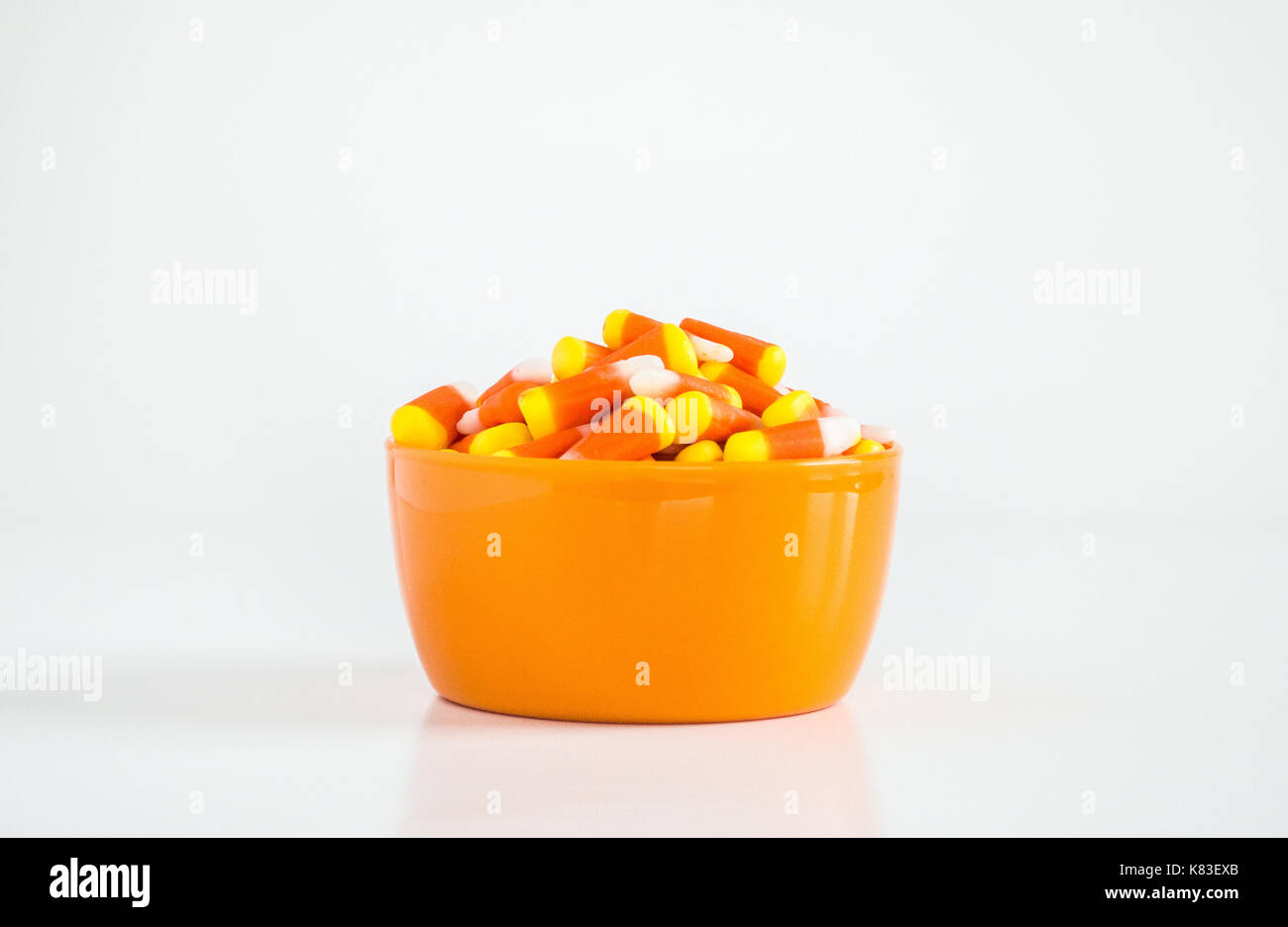 candy corn in an orange bowl isolated on white - Stock Image