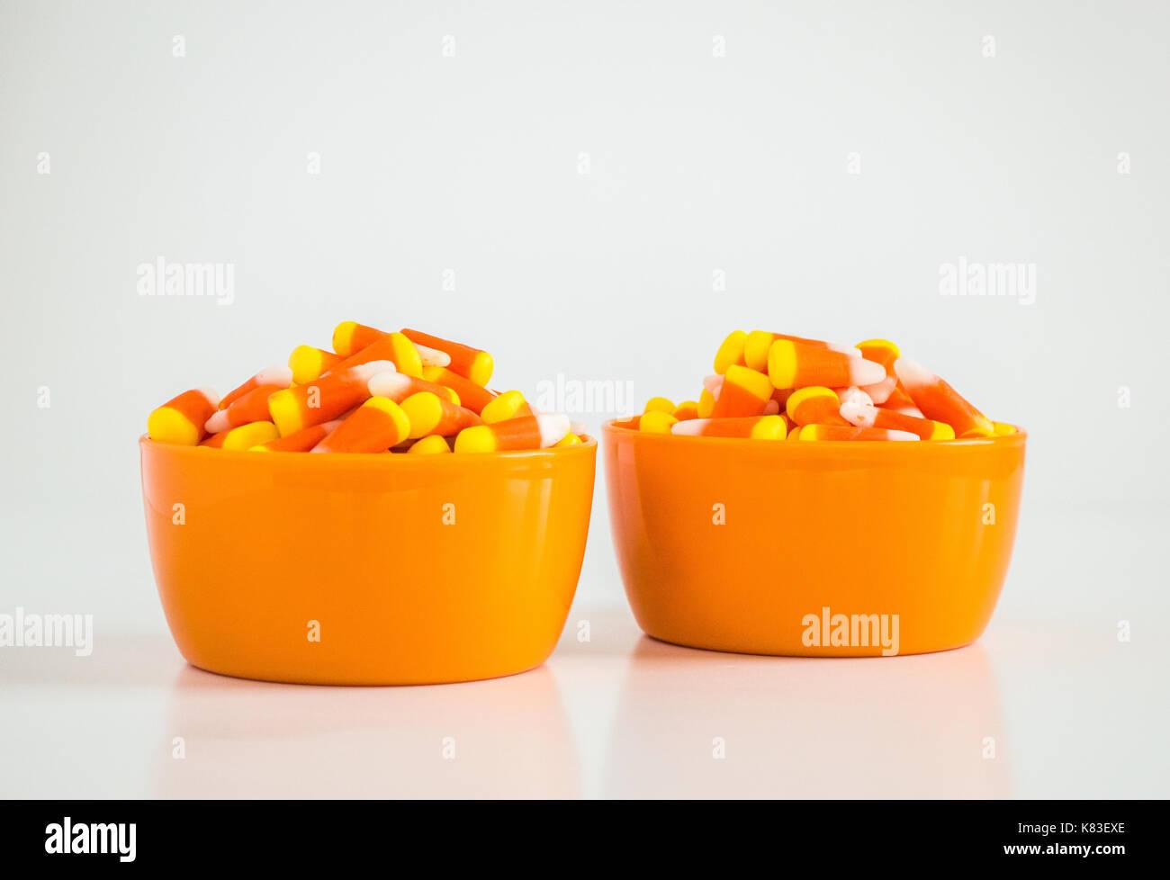 2 orange bowls of candy corn isolated on white - Stock Image