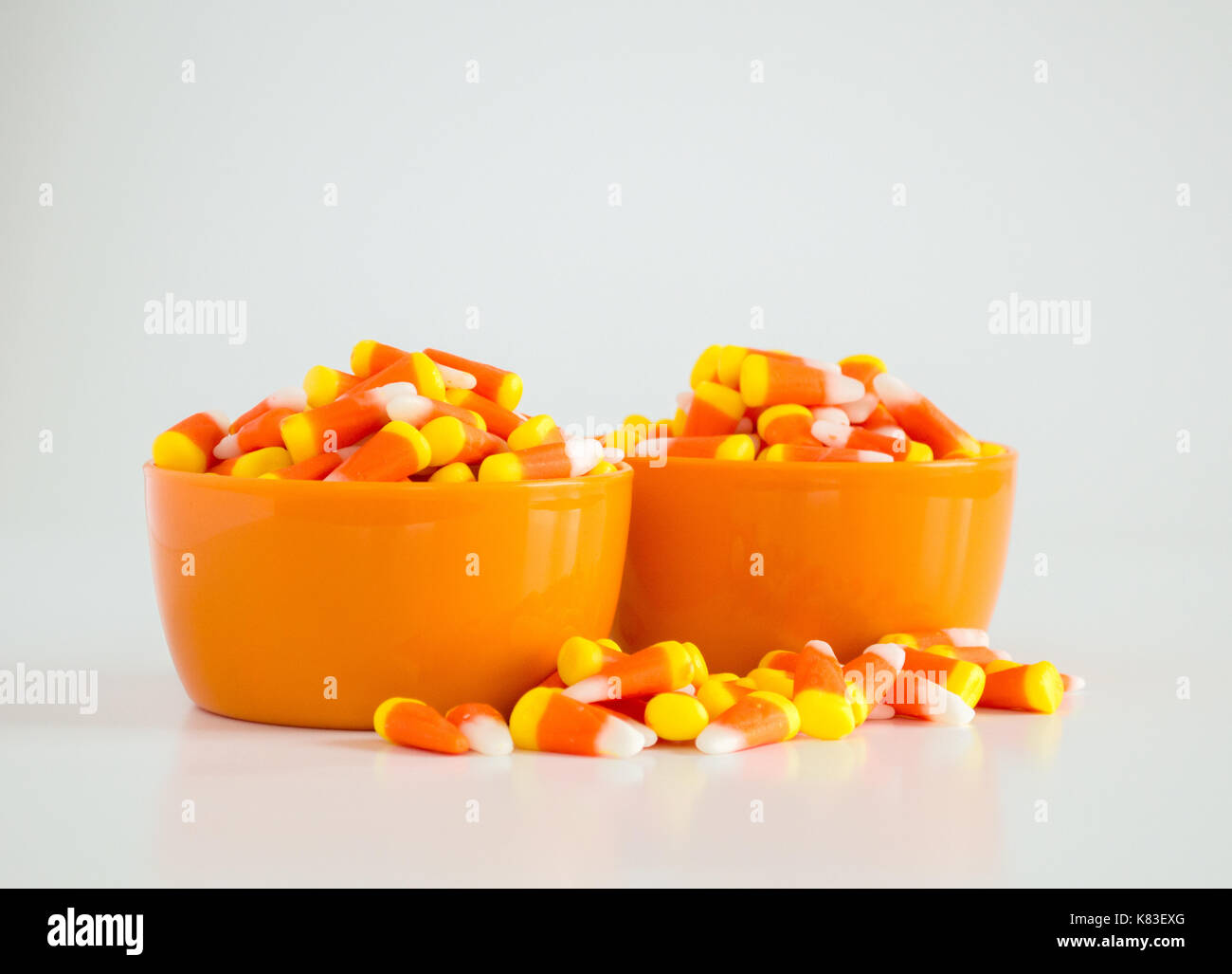 2 orange bowls of candy corn with overflow isolated on white - Stock Image