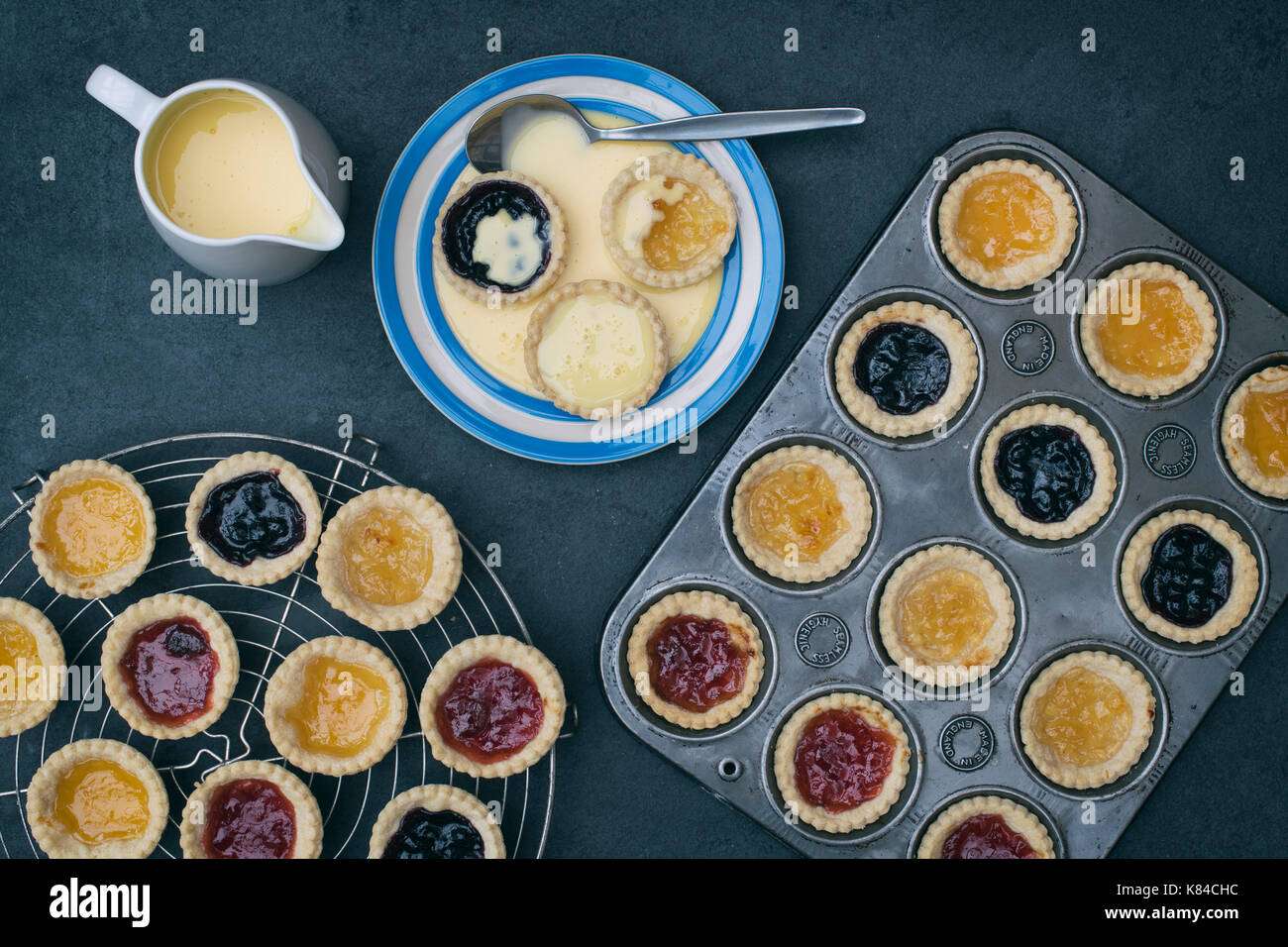 Cooked homemade jam tarts on a plate with custard next to a baking tray and a vintage circular wire rack - Stock Image