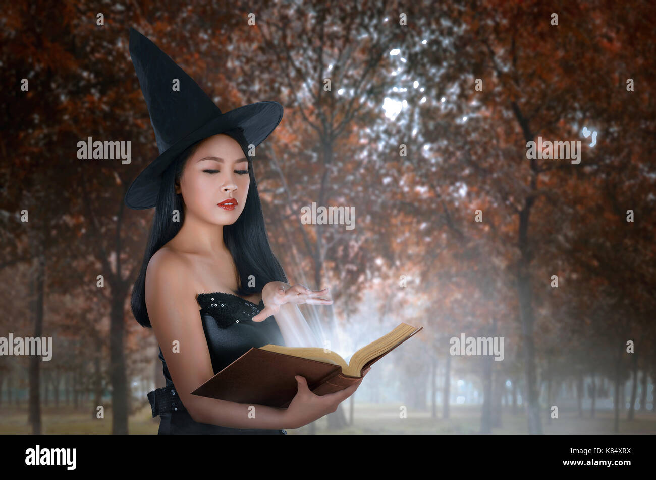 Young asian woman in witches costume holding spell book on the forest Stock Photo