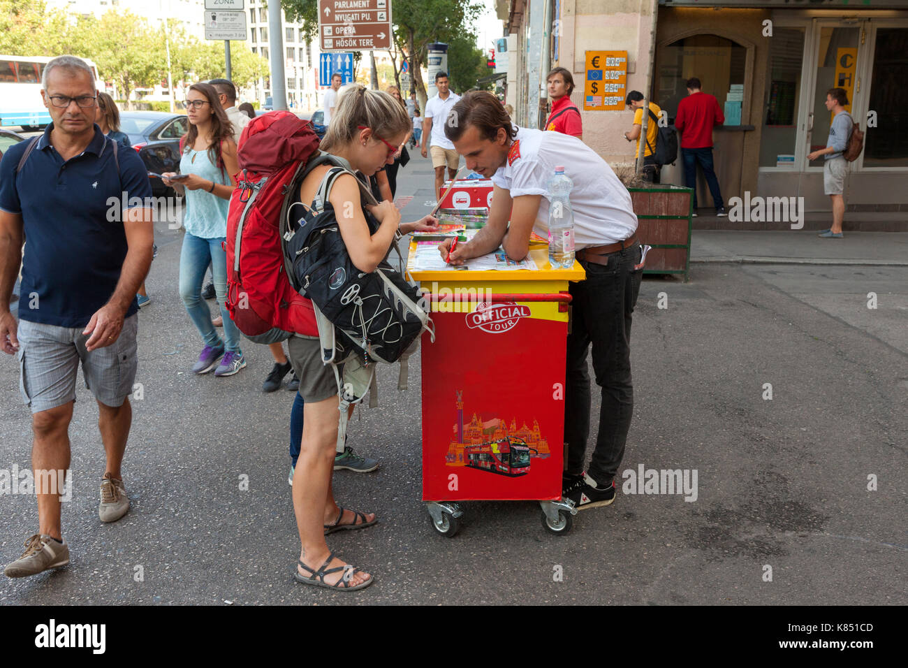 Backpackers at a city guide tour stand in central Budapest, checkin out optional tours. - Stock Image